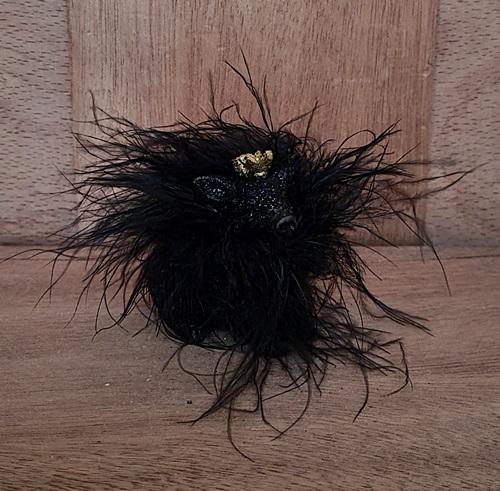 schwarzes schweinchen mit federboa